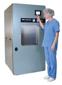 man in blue coat with hair net in front of a steam sterilizer